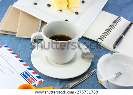 Clutter workspace with cup of coffee, blank note and pen, butter cake on white plate, letter envelope with scissors and cigarette in ashtray