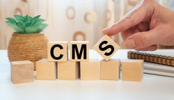 CMS concept. Wooden cubes with the abbreviation CMS Custom Management System