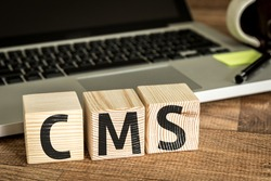 CMS (Custom Management System) written on a wooden cube in front of a laptop