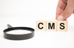 cms text wooden cube blocks and hand holding magnifying glass on table background.