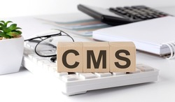 CMS written on a wooden cube on the keyboard with office tools