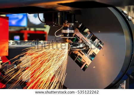 CNC laser cutting metal pipe with bright sparkle in factory. Industry machine.
