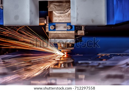 CNC Laser cutting of metal, modern industrial technology. Small depth of field. Warning - authentic shooting in challenging conditions. A little bit grain and maybe blurred. #712297558