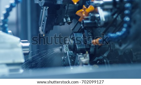 CNC milling machine is working and producing a metal detail. #702099127