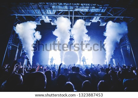 Co2 Smoke Cannons Silhouette of Crowd at a Music Festival  silhouettes of concert crowd in front of bright stage lights. Dark background, smoke, concert  spotlights