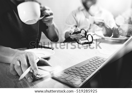 co worker website designers working at office and holding a cup of coffee with smart phone and digital tablet computer docking on smart keyboard,black white           #519285925