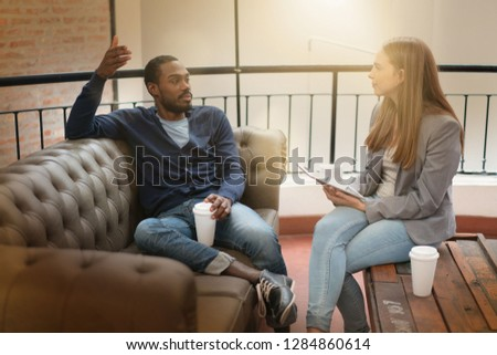 Co workers casually discussing ideas on sofa in modern workplace