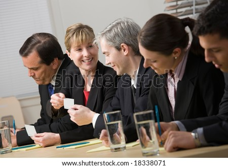Co-workers exchanging business cards while sitting on panel