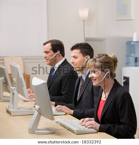 Co-workers in headsets working at computers in call center - stock photo