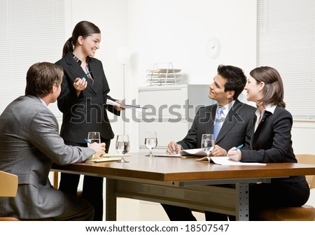 Co-workers listening to supervisor explain issue in conference room