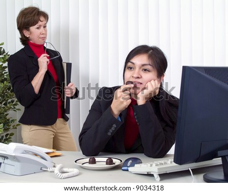 Co-workers on the job, one dreamily enjoying chocolate, the other annoyed by what she sees.