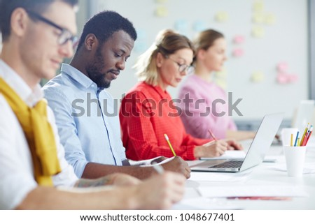 Co-working managers making notes while sitting in row in office or boardroom #1048677401