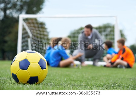 Coach  And Team Discussing Soccer Tactics With Ball In Foreground