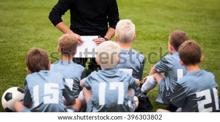 Coach Encouraging Boys Soccer Team. Soccer Football Team with Coach at the Stadium. Coach with Youth Soccer Team. Boys Listen to Coach\'s Instructions. Coach Giving Team Talk
