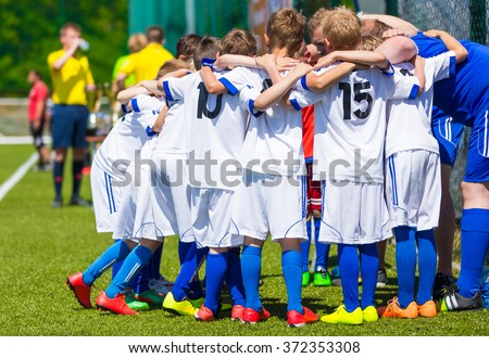 Coach giving young soccer team instructions. Youth soccer team together before final game. Football match for children. Boys group shout team, gathering. Coach briefing. Soccer football background.