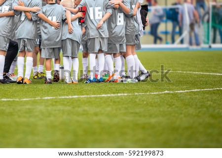 Coach giving young soccer team instructions. Youth soccer team together before final game. Football match for children. Boys group shout team, gathering. Coach briefing. Soccer football background
