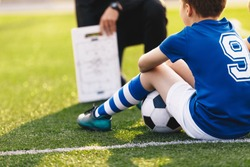 Coach trainer teaching kids on football field. Football coach coaching children. Soccer football training session for children. Football tactic education. Coach explains a game strategy using board