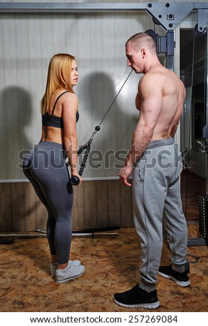 Coach with a client in the gym. Sports Man and athletic girl engaged in fitness in the gym.