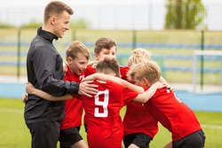 Coaching Youth Sports. Kids Soccer Football Team Huddle with Coach. Children Play Sports Game. Sporty Team United Ready to Play Game. Youth Sports For Children. Boys in Sports Jersey Red Shirts