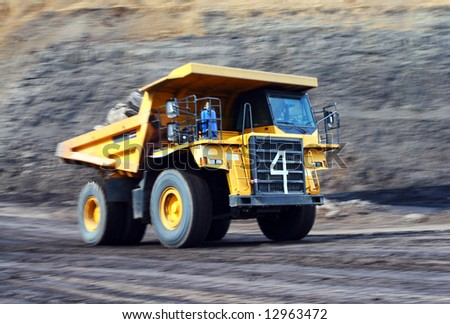 Coal dump truck working hard at site. Motion blurred panning shot.