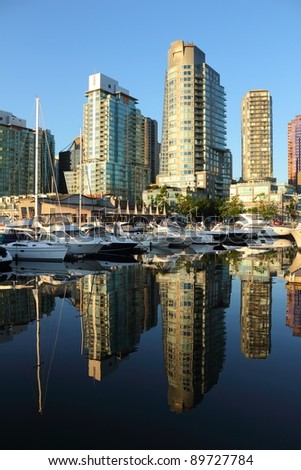Coal Harbor Condominiums reflect the early morning light in the calm water of the marina across from them. Vancouver, British Columbia, Canada.