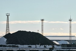 Coal heap, natural black coal, product of mining and three towers with searchlights. Industrial landscape with pile of carbon material. Global warming, CO2 emission, coal energy. Winter scene.