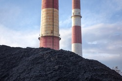 Coal heap, natural black coal with industrial chimney. Industrial landscape with pile of carbon material. Global warming, CO2 emission, coal energy issues. Coal mine in Katowice, Poland.
