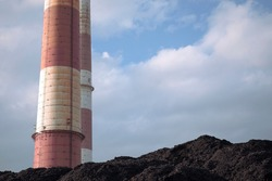 Coal heap, natural black coal with industrial chimneys and blue clouds sky. Industrial background. Global warming, CO2 emission, coal energy issues.