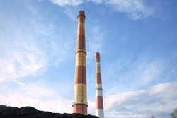 Coal heap, natural black coal with industrial chimneys and blue clouds sky. Industrial background. Global warming, CO2 emission, coal industry, energy from fossil fuels, air pollution issues.