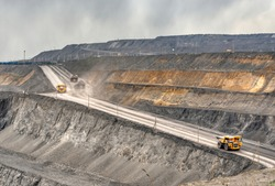 Coal mine, aerial view. Road for the movement of mining trucks. Ways to transport minerals to the surface of the earth. A mining truck is driving along a mountain road.