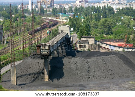 Coal mine and railway cars waiting to be loaded - stock photo