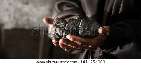 Coal mining : coal miner in the man hands of coal background. Picture idea about coal mining or energy source, environment protection. Industrial coals. Volcanic rock. Panorama photo