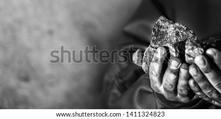 Coal mining : coal miner in the man hands of coal background. Picture idea about coal mining or energy source, environment protection. Industrial coals holding on hands. Volcanic rock. Panorama photo