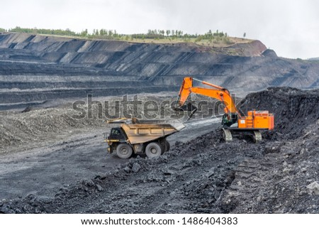 Coal mining in a quarry. A hydraulic excavator loads a dump truck. Loading of minerals and mining truck.