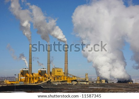 Coal  Power Plant emitting pollution. with blue skys and  snow