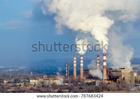 Coal power plant smokestacks emit carbon dioxide pollution by factory under blue sky. environmental pollution