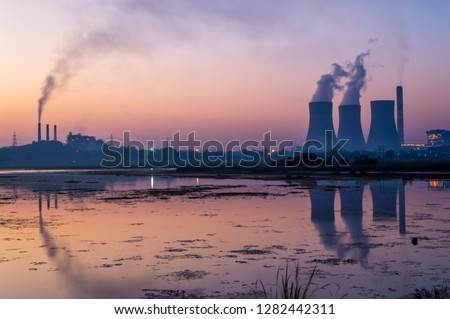 Coal powered thermal power plant. Chimney emitting smoke and cooling tower emitting steam. The lake near the electricity generating power plant showing reflections.
