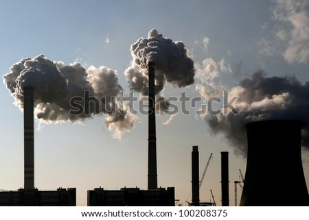 coal smoking power plant against the sun