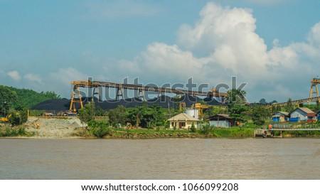 coal stockpile with conveyor on Mahakam riverbank, Indonesia #1066099208