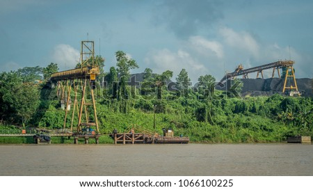 coal stockpile with conveyor on Mahakam riverbank, Indonesia #1066100225