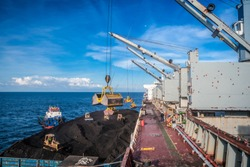Coal transfer from vessel to a mother vessel using crane in the middle of the sea