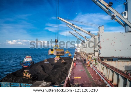 Coal transfer from vessel to a mother vessel using crane in the middle of the sea #1231285210