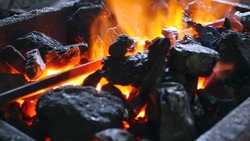 Coal with burning fire and iron.