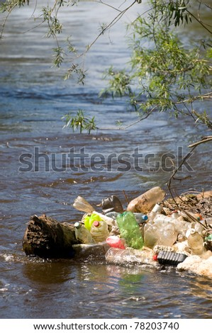 Coast and garbage plastic bottles damage river after flood in Poland. Scatter empty plastic bottles stuck on log in water under small twigs of bush, dump environment, objects spilled out, vertical