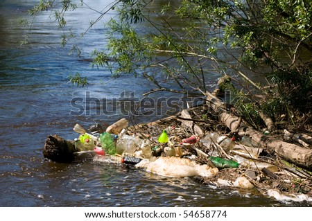 Coast and plastic bottles garbage damage river after flood in Poland. Scatter empty plastic bottles stuck on log in water under small twigs of bush, dump environment, objects spilled out, horizontal.