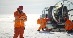 Coast guard team standing on frozen lake with hovercraft on background. Rescuers in safety uniform loading equipment in airboard preparing to patrol arctic area