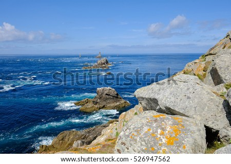 Coast in Brittany, with cliffs at the top of cliffs, Rocky promontory Pointe du Raz #526947562