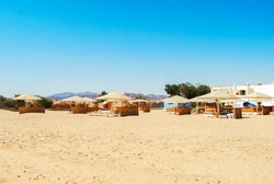 Coast of Africa, Safaga, Egypt. Beach line with straw umbrellas, sun beds and white sand. Vacation at the sea.