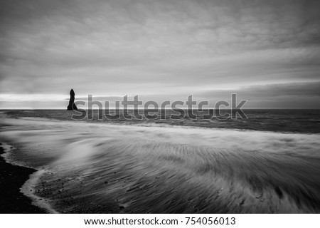 Coast of the Atlantic Ocean. Vic Beach in Iceland with black sand and a lonely rock in the sea. The wave ran up to the shore, a long exposure. Black and white photo.  #754056013