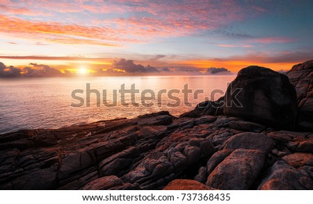 Coast sea. Sunset. Wild rock beach. The natural rock formation. Red sun over summer sea. Cloud on a blue sky over summer sea. Mountains in thailand